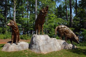 A bronze wolf atop a rock howls as two other wolves crouch on the lookout.