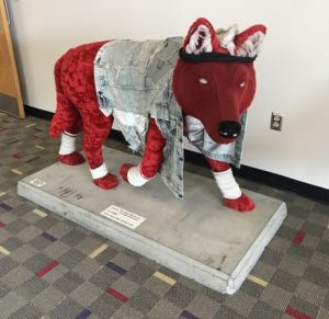 Plush red wolf sculpture outfitted in ripped denim jacket