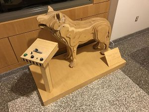 Wooden mechanical wolf sculpture, layered like a topographical map.