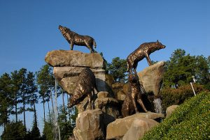 Seen from below against a clear blue sky, four bronze wolves, each with a different pose, clamber over a large, rocky hill.