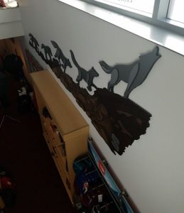 Wall art of a parade of 5 wolves climbing a cliff